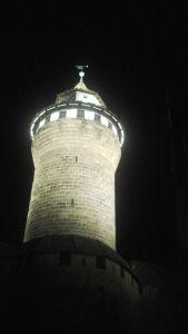 Taghell erleuchtet ragt der Turm der Nürnberger Burg in die Höhe.