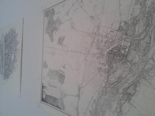 """Im Vordergrund der """"Plan der königlichen Residenzstadt München"""", im Hintergrund der Stadtplan Würzburgs"""