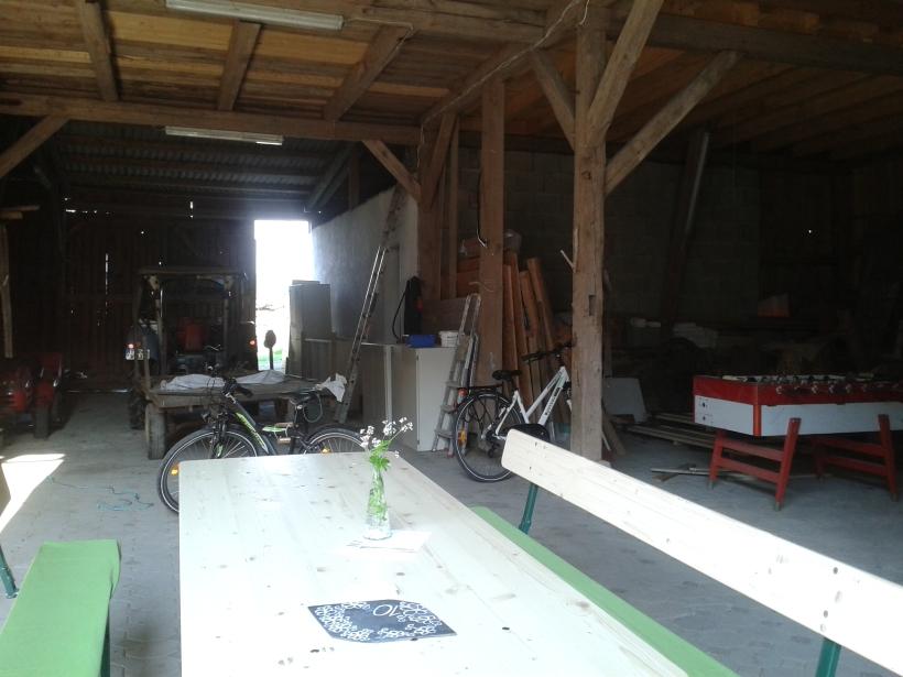 Ein Tisch steht in einer Scheune. Hinten raus geht's ins Grüne, das könnte künftig evtl ein Biergartenplatz werden.