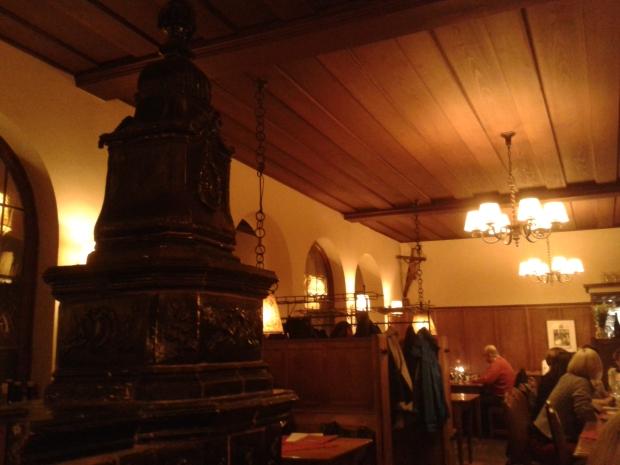 Der Ofen schaut nach Renaissance aus, das Kruzifix stammt vom Bildhauer Hans Schiestl.