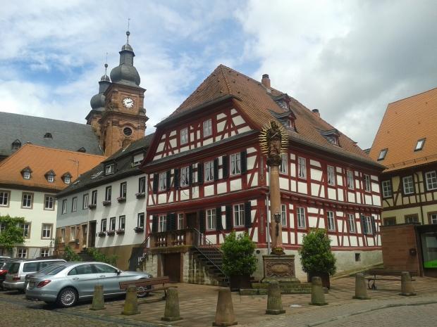 Amorbach hat einiges an Fachwerk zu bieten, links die katholische Pfarrkirche St. Gangolf.